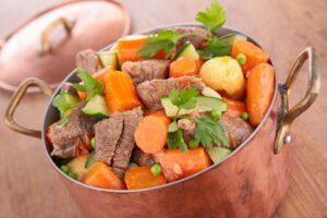 Casseruola in rame ricolma di manzo, patate e verdure per il cane