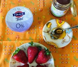 ingredienti per lo spuntino: miele, yogurt, fragole.