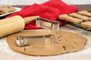tavola con impasto per biscotti per cani, mattarello e forme biscotto ad osso