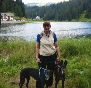 Elena con i suoi due levrieri neri, Silverina e Rory, sullo sfondo del lago di carezza.