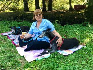 Elena dseduta su una coperta con due levrieri neri. Silever e Rory guardano il panino che ha in mano, mentre lei sorride.