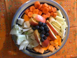 un piatto scon tutte le verdure e la frutta, tagliate a fette, per essere cuscinate. Il piatto è adagiato su una tovaglietta arancione a fantasia