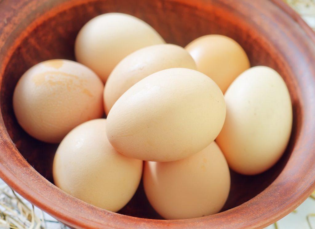 primo piano di una ciotola in coccio, contenente uova di gallina crude