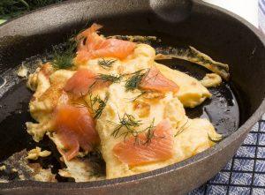 omelette per cani, con salmone e aneto, in una padella nera