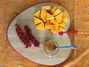un tagliere a forma di cuore ospita della zucca arancione a dadini, due rametti di riber e una tazzina con del miele. Il tagliere poggia su una tovaglia arancione