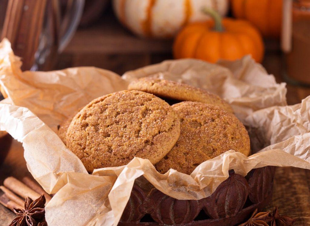biscotti alla zucca e cannella in un cestino marrone, con sullo sfondo delle piccole zucche arancioni